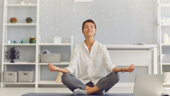 A woman is shown meditating.