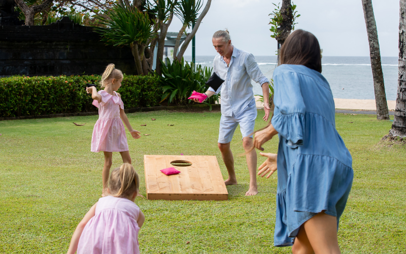 A family plays cornhole in their yard